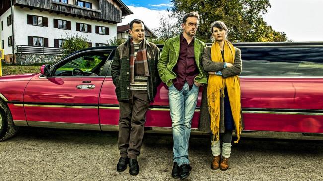 Gruppenphoto mit Geltinger Schwindler-Trio vor farbiger Strechlimousine: Gerhard Wittmann (Karl Kainz), Sebastian Bezzel (Hubertus Hochstetter) und Kathrin von Steinburg (Iris Schranner)