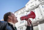 Franz Hubert (Christian Tramitz) spricht über das Megaphon mit der lebensmüden Anna Schmitt, die von ihrem Balkon springen will.