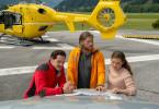 Tobias (Markus Brandl, l.), Markus (Sebastian Ströbel, M.) und Lara Fellner (Leonie Rainer, r.) besprechen am Heliport die weitere Vorgehensweise.