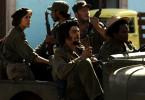 Che (Benicio Del Toro) fährt mit Aleida (Catalina Sandino Moreno) und weiteren Gefolgsleuten in eine eroberte Stadt ein.