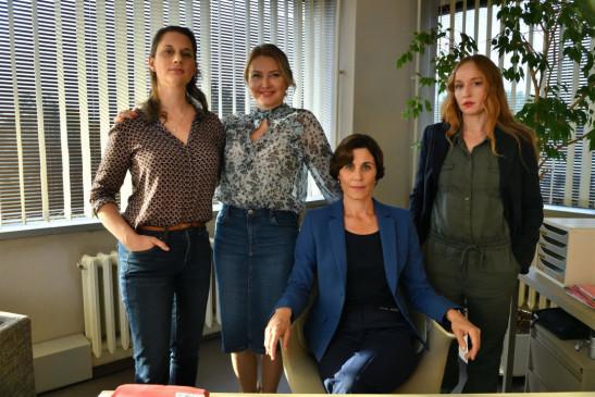 Karin Lichtness (Nina Kunzendorf, M.) versammelt Iris Doppelbauer (Brigitte Hobmeier, r.) und weitere weibliche Kolleginnen für ein gemeinsames Pressefoto, um die Frauenpower des Teams darzustellen.